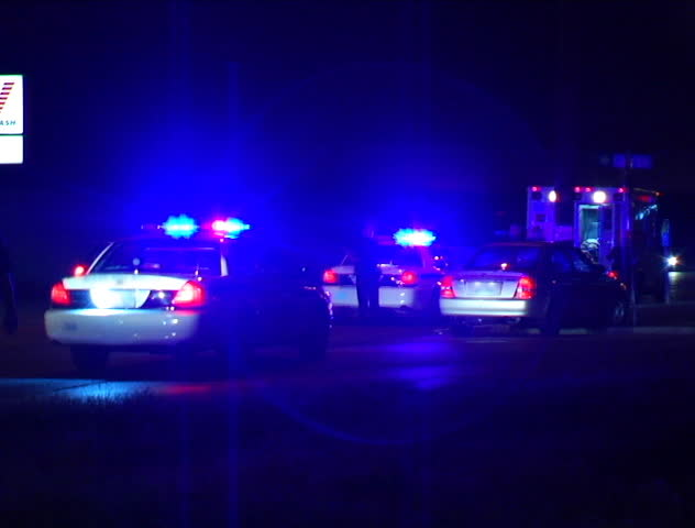 Two Police Cars And An Ambulance Flash Their Lights At