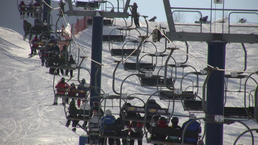 A ski lift is slowly transporting people to the top of the ski hill. (High Definition) | Shutterstock HD Video #27602
