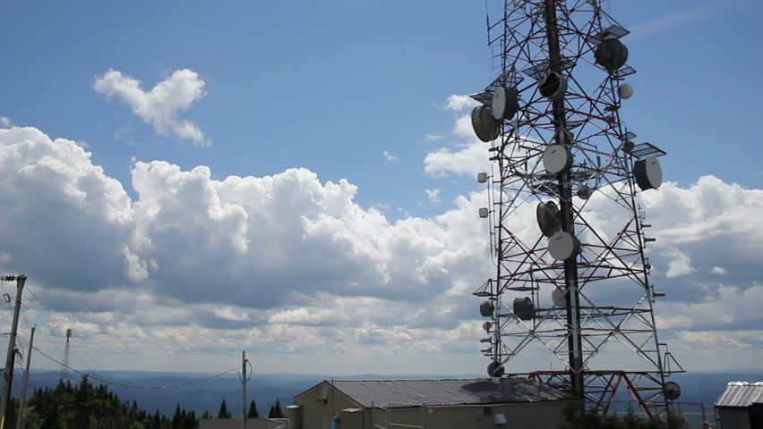 Telecommunications Tower 01 Tilt up at the bottom of a communications tower, with a blue sky and some clouds. - HD stock footage clip