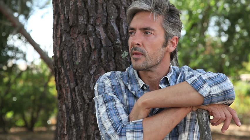 Portrait of middle-aged man relaxing against tree