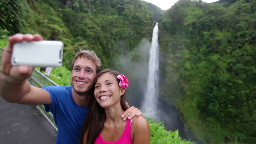 Couple tourists taking self portrait with camera phone on Hawaii, Big Islands, Akaka Falls. Happy cheerful young multicultural couple on travel.