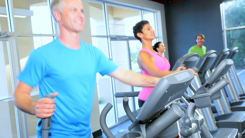 Health club members keeping fit using modern exercise equipment - HD stock footage clip