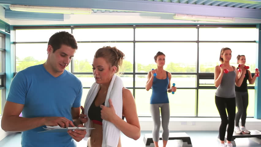 Woman talking with trainer at aerobics class in gym
