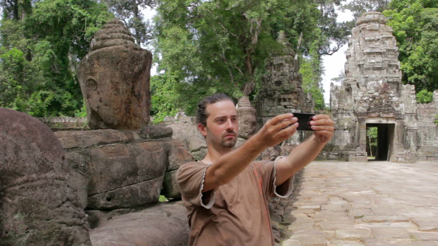 a lone visitor takes own picture in preah khan temple, Angkor - HD stock video clip
