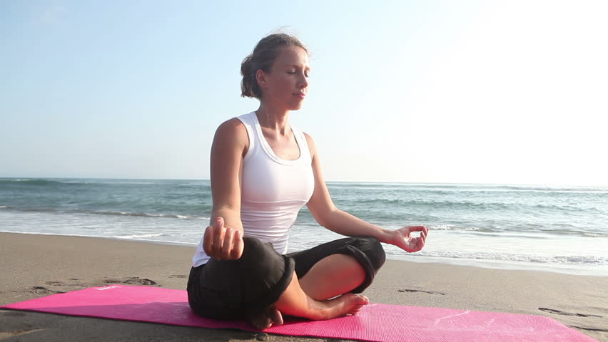 Spirituality woman sitting in lotus pose at coastline - HD stock video clip