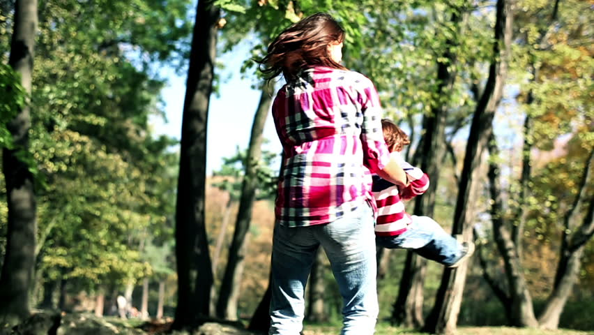 Young mother having fun with her son in beautiful autumn park, slow motion