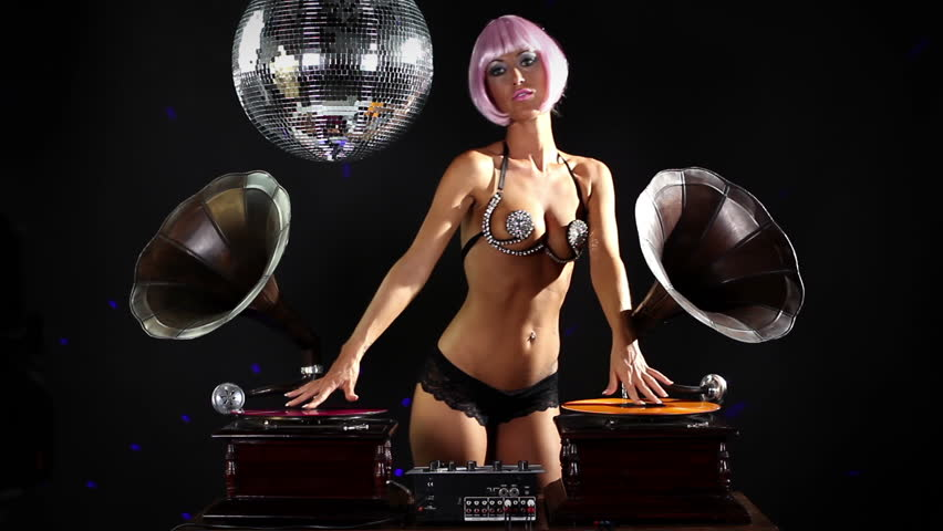sexy professional gogo shot dancing and posing behind gramophone dj turntables. cool and quirky disco shot