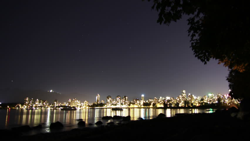 A Starry Night looking at Downtown Vancouver, BC, Canada. Boats Floating on the ocean as Stars rotating in the sky. Shot in 4k RAW photo sequence