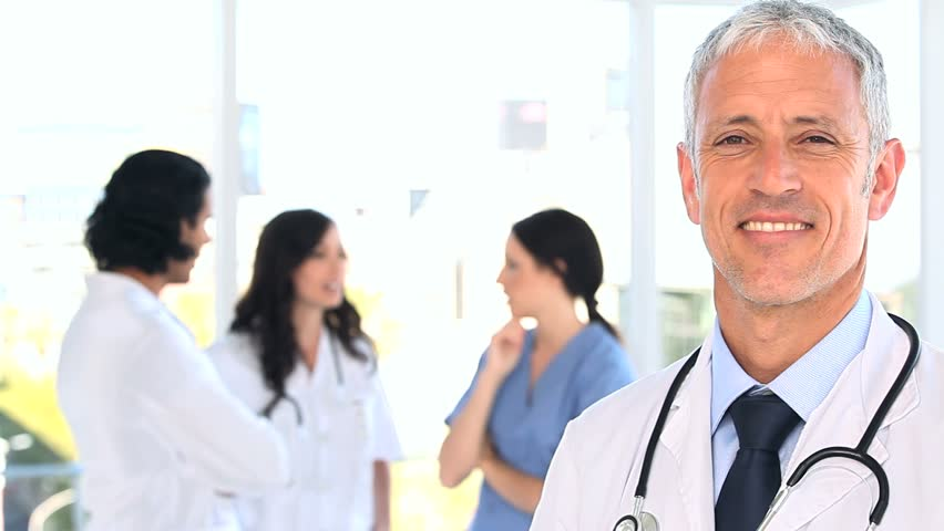 Happy mature doctor standing in front of his team in a bright room - HD stock footage clip