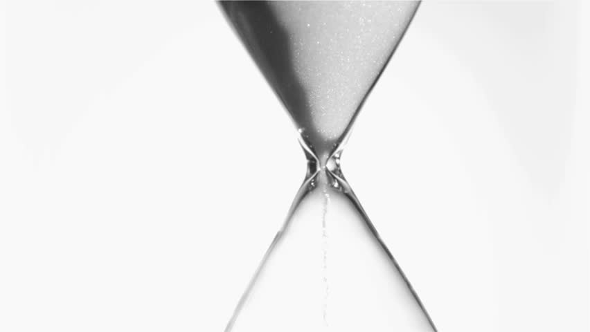 Sand flowing in super slow motion from an egg timer against a white background - HD stock footage clip