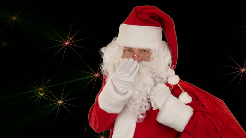 Santa Claus carrying his bag, is looking at the camera and sends a kiss with golden stars