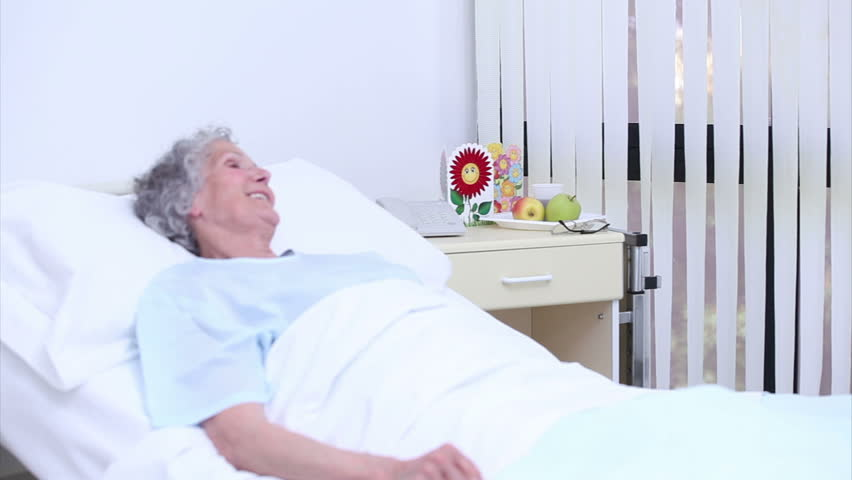 Serene senior woman at a nurse who gives a bouquet of flowers in a hospital room - HD stock footage clip