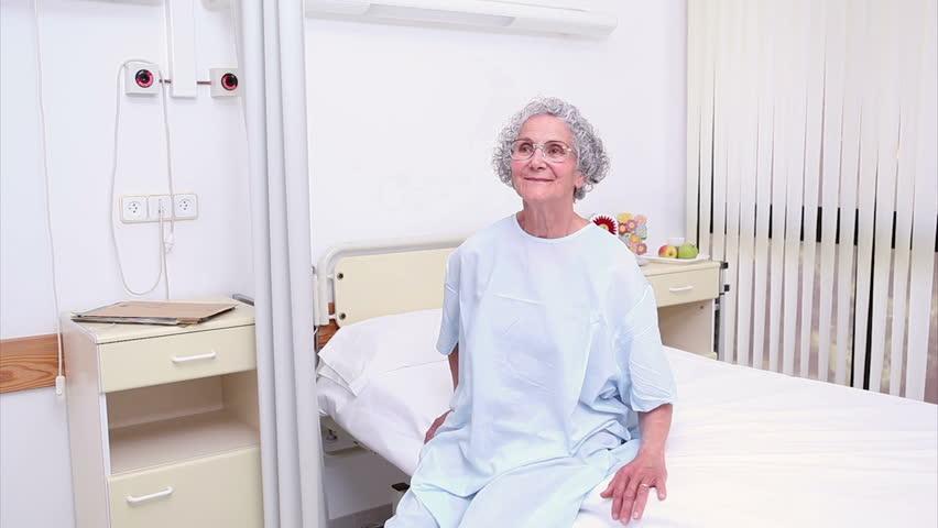 Nurse assisting an elderly patient in hospital ward - HD stock footage clip
