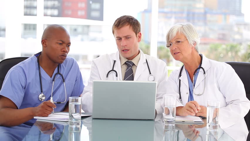 Mature doctor sitting with her team while looking at a laptop in a bright room - HD stock footage clip