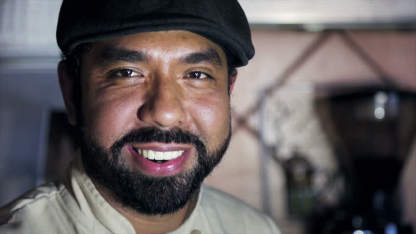 Bearded male Latin Barista in his Coffee shop smiling