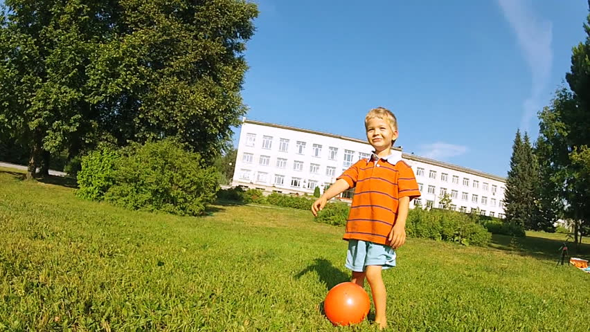 Young boy playing with a ball on a hot summer day