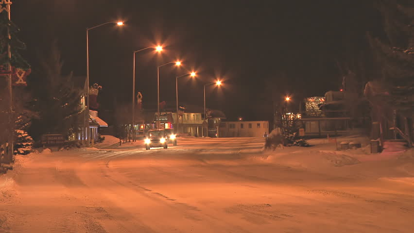 HOMER, AK - CIRCA 2011: Minimal traffic at night in a small town on snow-covered roads in the middle of winter. - HD stock video clip