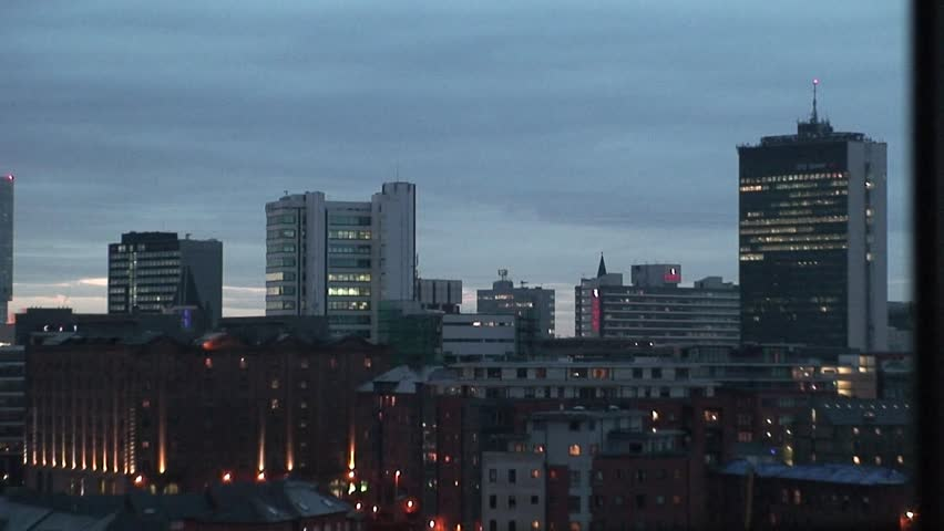 Timelapse shot of Manchester City Centre skyline as it goes dark and building lights are turned on.