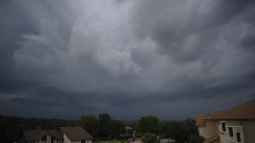 Time lapse of a big dark storm blowing over a town at dusk, with lots of clouds, wind, rain and lightning. - HD stock footage clip