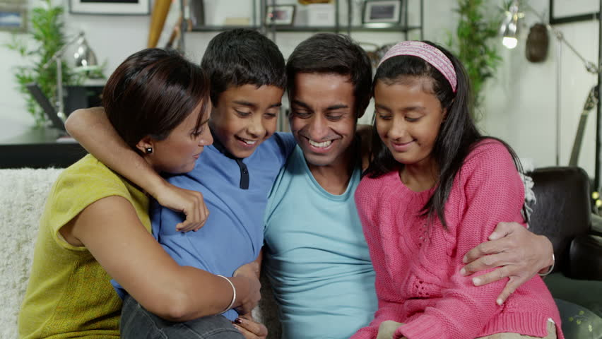 Happy family of 4 seated together at home. They are laughing and hugging.