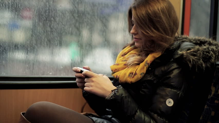 Young woman using smartphone while riding tram, steadicam shot