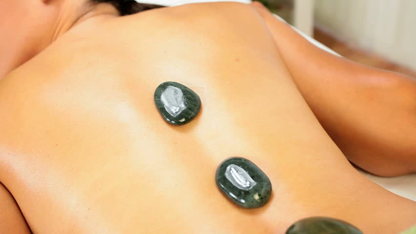 Beautiful ethnic client being treated with hot stone therapy at a luxury health spa - HD stock footage clip