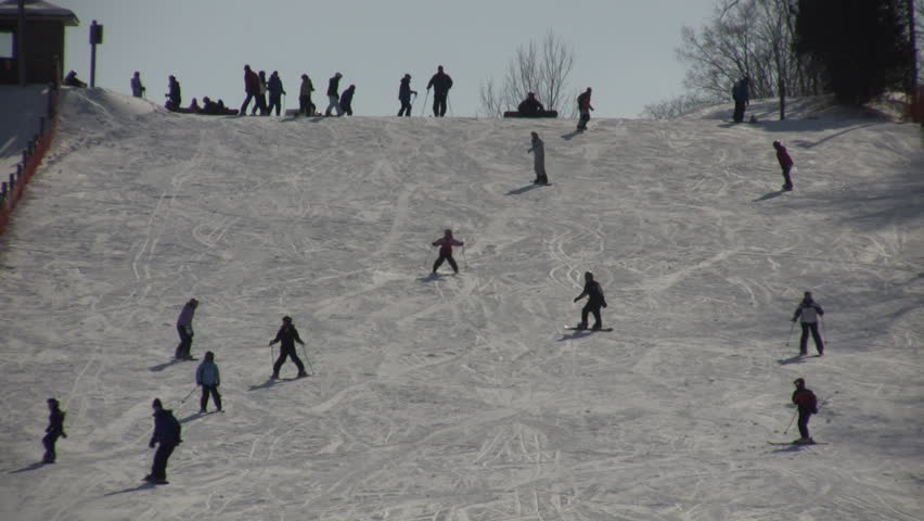 Winter scenic of people skiing down a hill on a sunny day (High Definition) - HD stock video clip