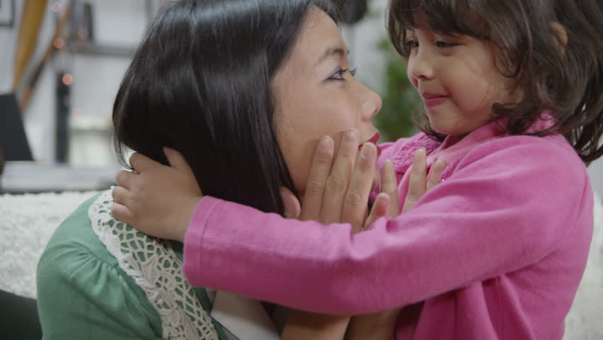 A woman is upset and worrying about events in her life which are beyond her control. Her small daughter comes to her to give her a hug and to smile at her to cheer her up. In slow motion.