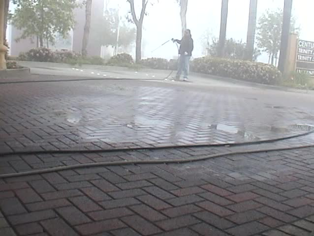an unidentifiable person shows how to expertly power wash or Steam Clean a parking lot - SD stock video clip