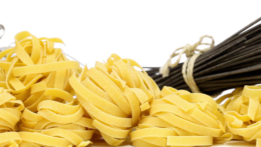 Collection from mixed uncooked raw pasta - spaghetti, farfalle, tagliatelle and black spaghetti