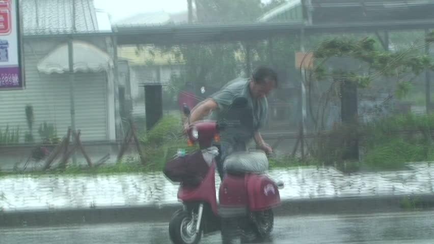 HUALIEN, TAIWAN - AUGUST 2009: Man lashed by ferocious wind and rain of typhoon Morakot. - HD stock footage clip