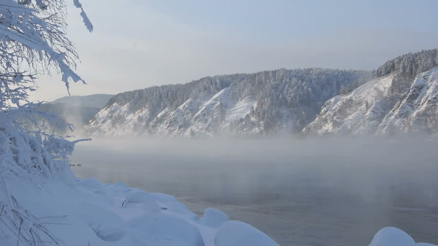 Yenisei River Winter Landscape 02. View of the Siberian Yenisei River in sunny frosty day. Hilly coast, snow-covered forest, vapor flux moving over the surface of the water. January 12, 2013. - HD stock footage clip