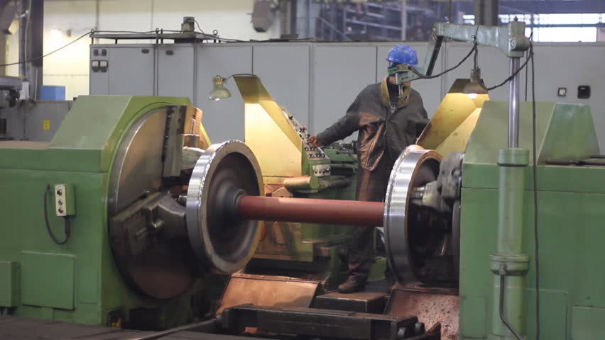 Worker on a machine, metal working lathe a in factory. Machining process in the factory for repair of trains and wagons - HD stock footage clip
