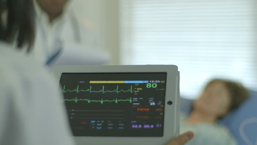 A doctor or nurse in a hospital setting looks at the vitals and other data being displayed on a portable patient monitor she is holding. - HD stock video clip