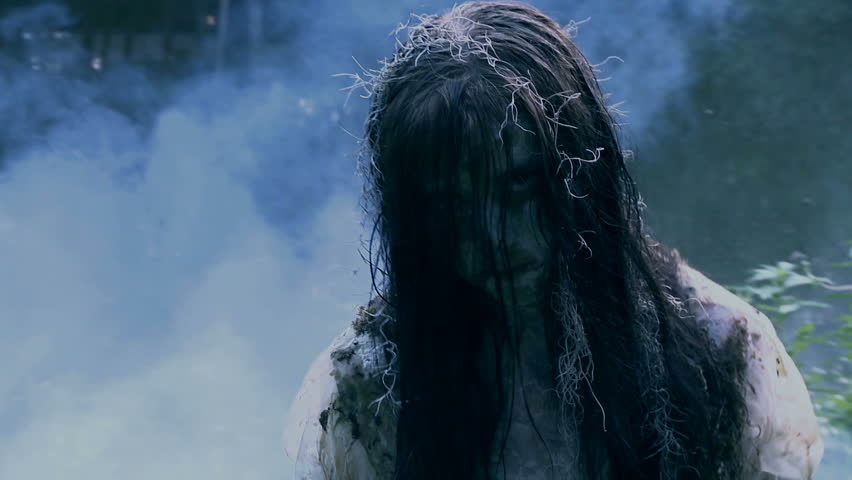walking through fog an undead zombie girl possessed with evil attacks the camera  - HD stock video clip