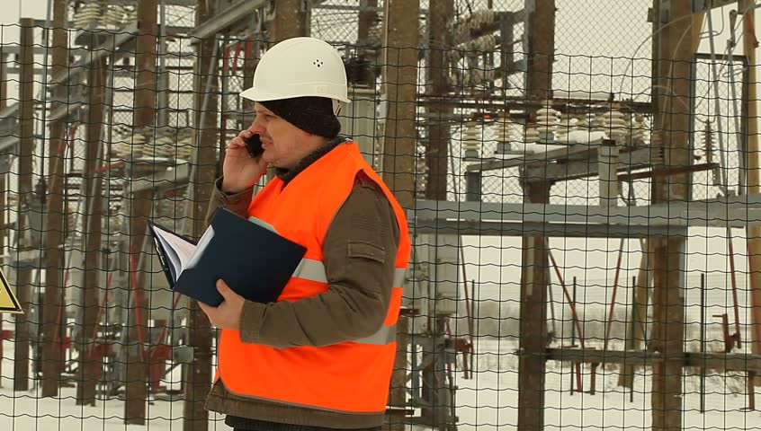 Engineer talking on the phone at the electrical substation - HD stock video clip