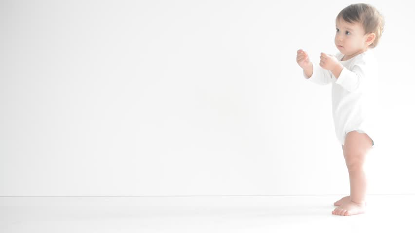 Happy little baby making first steps on white floor