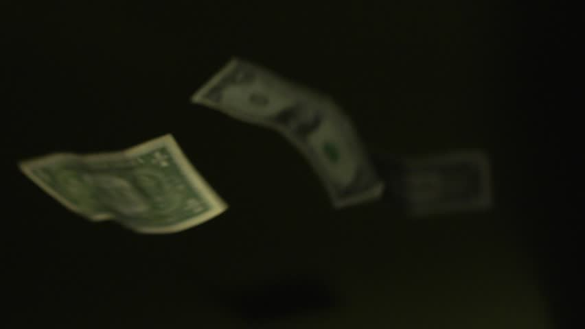 Raining Money Bills fall down on a black background. Not animated. Shot at high shutter speed.  - HD stock video clip