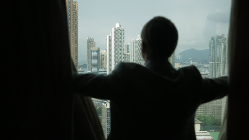 Man opens curtains on the view Hong Kong