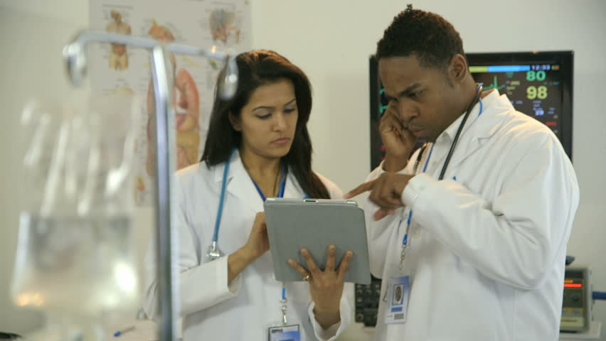 Focus moves from an IV bag solution in the foreground to two physicians consulting what they are studying on an electronic tablet pc. - HD stock video clip