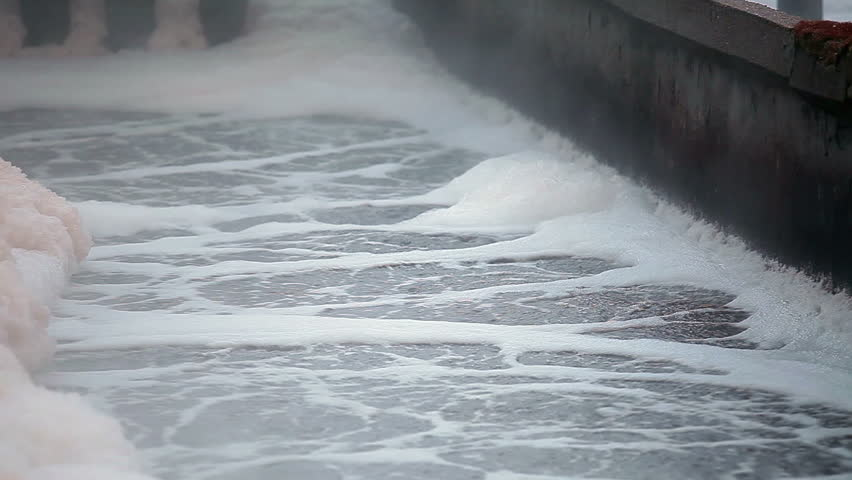 Close up of foam on swirling waste water surface in aeration tank