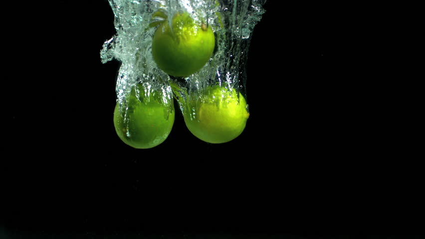Three limes dropping into water in slow motion