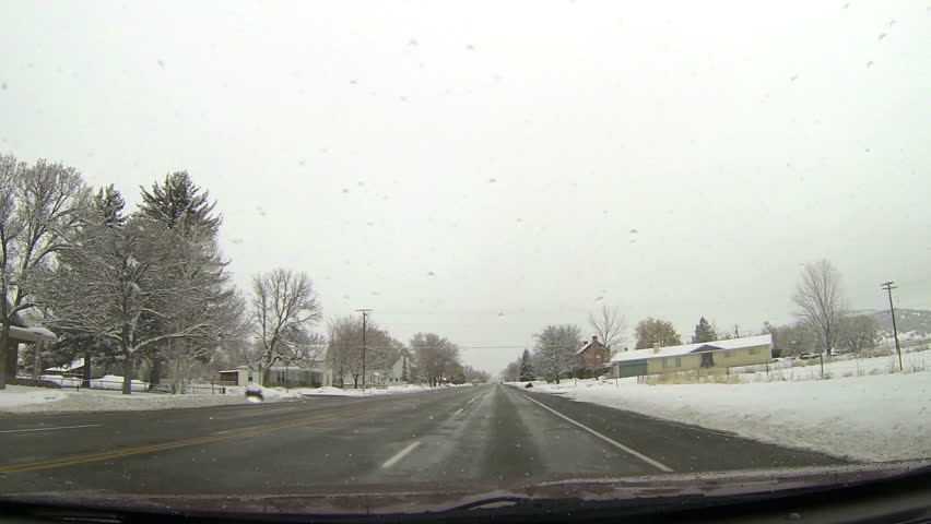 Winter snow rural town main street. Driving a car on rural country road in winter. Snow and ice on highway and near mountains and hills. First person point of view through windshield. | Shutterstock HD Video #3368528