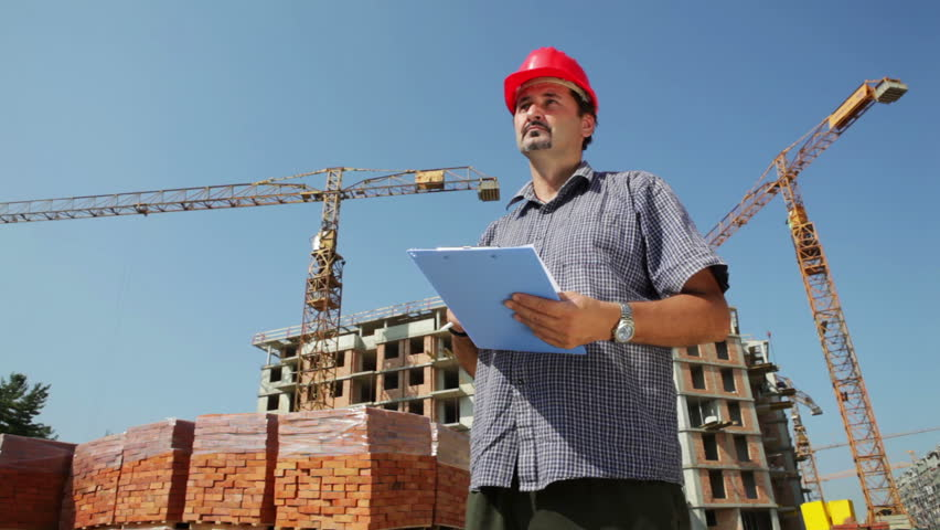 Construction architects review plans at a construction site with crane. - HD stock footage clip