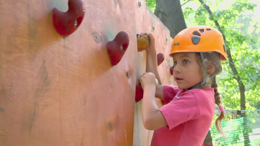 Rock climbing. Little girl in helmet crawls on pendant wall in outdoor climbing center, closeup - HD stock footage clip