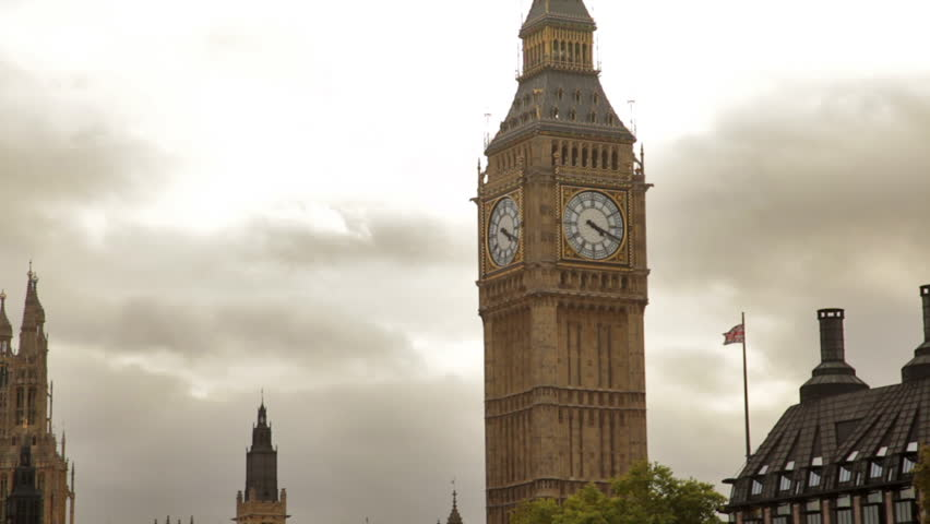 Big Ben tower with white storm clouds behind it in London, England.