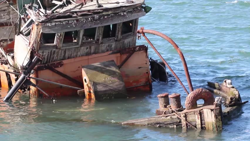 Vintage abandoned rotting trawler boat bobbing in harbor waters - HD stock video clip