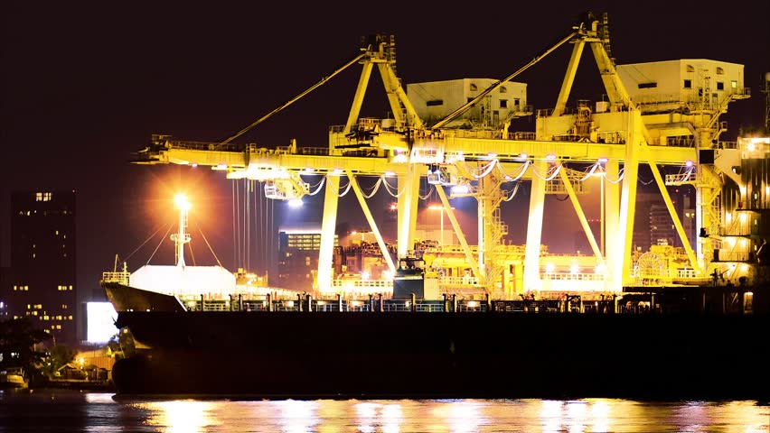 Industrial Container Cargo freight ship with working crane bridge in shipyard at dusk for Logistic Import Export