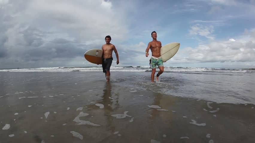 Two happy young surfers holding their surf boards and walking #3467222