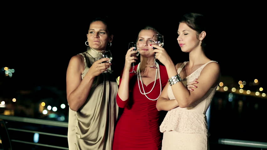 Three female friends enjoying night party on the terrace, crane shot  - HD stock footage clip